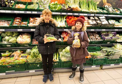 Børn foran grøntsagerne i supermarkedet